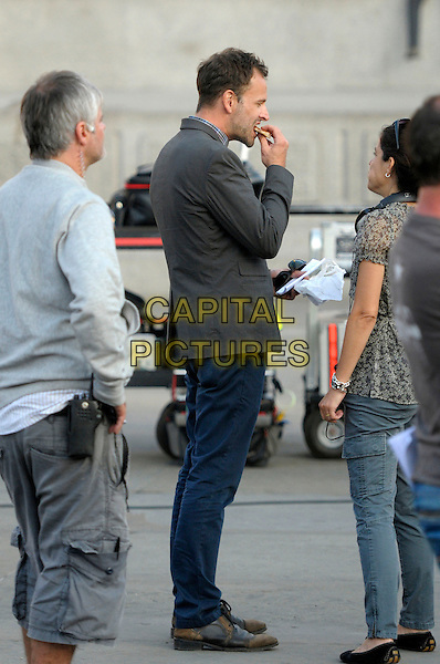 Jonny Lee Miller<br /> Filming on the set of &quot;Elementary&quot;, Trafalgar Square, London, England.<br /> July 10th, 2013<br /> cast crew tv series show full length eating food grey gray suit jacket side profile    <br /> CAP/IA<br /> &copy;Ian Allis/Capital Pictures