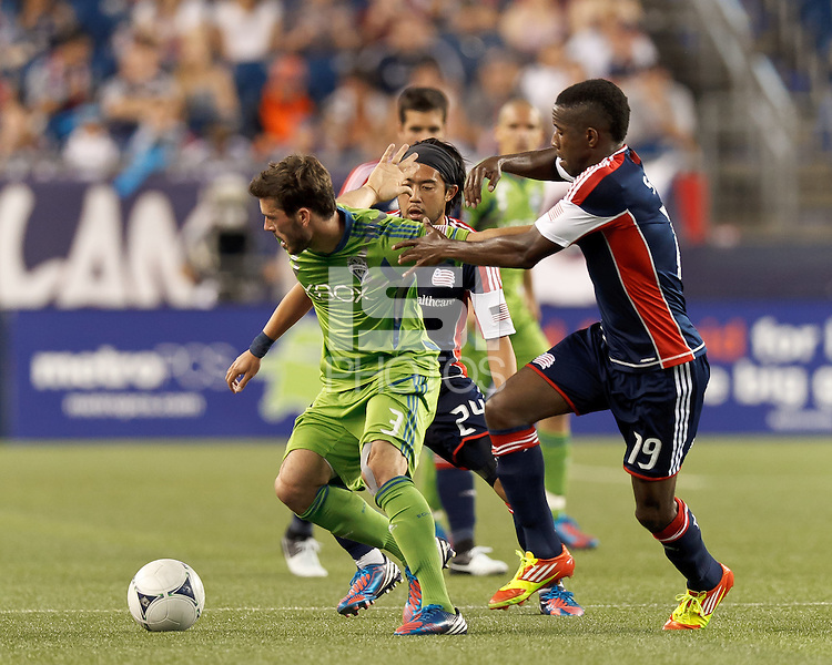 Seattle Sounders FC midfielder Brad Evans (3) dribbles as New England Revolution midfielder Lee Nguyen (24) and New England Revolution midfielder Clyde Simms (19) pressure. In a Major League Soccer (MLS) match, the New England Revolution tied the Seattle Sounders FC, 2-2, at Gillette Stadium on June 30, 2012.