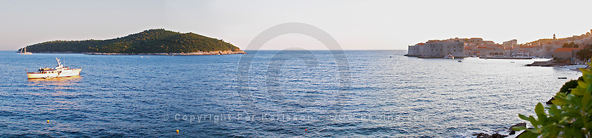 Panoramic view over the old town and the island Lokrum and a luxury cruising boat on the sea in evening light the sun setting from the luxury Excelsior Hotel and Spa restaurant terrace Dubrovnik, old city. Dalmatian Coast, Croatia, Europe.