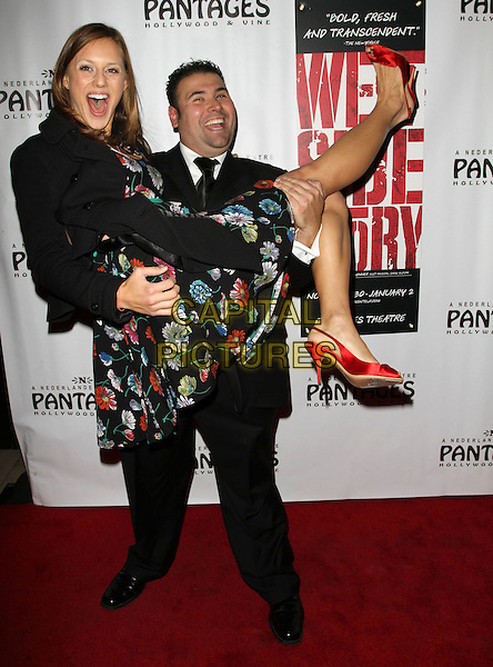 BENNY AGUAYO & GUEST.West Side Story Play Los Angeles Opening Night held At the Pantages Theatre, Hollywood, CA, USA..December 1st, 2010.full length black suit dress floral print lifting carrying .CAP/ADM/KB.©Kevan Brooks/AdMedia/Capital Pictures.