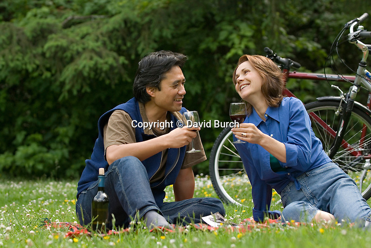 Couple having picnic, laughing, drinking wine