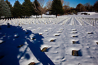 Grave markers and headstones surrounded by snow at Fort Logan National Cemetery, Denver, Colorado.