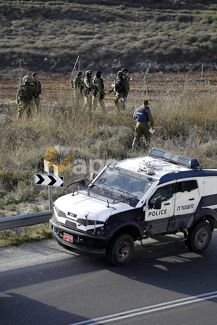 """Israeli security forces monitor the area as their colleagues give back the body of Haitham al-Bau, who was shot dead by Israeli soldiers after throwing a petrol bomb at a military jeep, to members of the Palestinian Red Crescent in the village of Halhul north of the Israeli occupied West Bank city of Hebron, on February 5, 2016. At least two Palestinians threw a Molotov cocktail at a military jeep on patrol close to Halhul north of the West Bank city of Hebron, a military spokeswoman said. Responding to an """"immediate threat"""", the soldiers fired on them, killing one. The other was arrested, she said. Photo by Wisam Hashlamoun"""