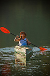 Woman kayaking and bird watching on Sugar Pine Reservoir, near Foresthill, California.