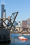 A tow boat pushes a load of rock down the Chicago River.
