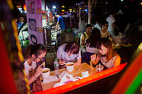 "A group of students from Hubei Province eat fried noodles from a franchise food vendor at Deyi World plaza near the Jiafengbei central business district in Yuzhong district, Chongqing, China. The group, ages 18-20, had spent their summer vacation as volunteer teachers in Guizhou Province and stopped in Chongqing on the way back to their hometowns. Ge Xin Wei (in blue) said that they came to Deyi World because they'd heard the area was a popular place to go at night. ""The food is delicious and spicy,"" she said."