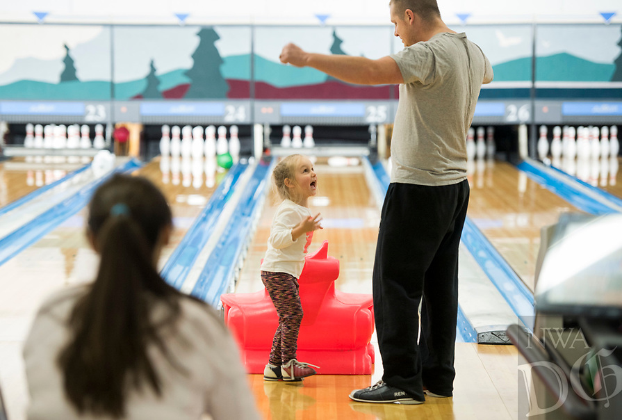 NWA Democrat-Gazette/CHARLIE KAIJO Josh Bishop of Bentonville (right) cheers with his daughter Molly Bishop, 3, while bowling, Sunday, February 11, 2018 at the Rogers Bowling Center in Rogers. Low temperatures left many of the roads icey. <br />