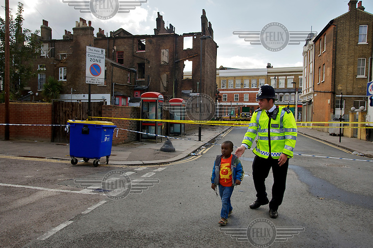 A policeman takes a small boy away from a cordoned area where rioting took place two nights earlier in Tottenham, London borough of Haringey. London saw the beginnings of riots on Saturday evening, after a peaceful protest in response to the shooting by police of Mark Duggan during an attempted arrest, escalated into violence. By the third night of violence, rioting had spread to many areas of the capital and to other cities around the country.