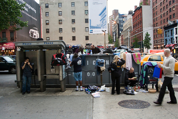 Freegans search through a dumpster outside New York University (NYU) for reusable refuse after the students move out for the summer.