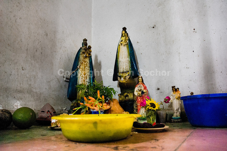A sacrificial spot belonging to the Afro-Cuban religious tradition placed on the floor in the corner of a house in Santiago de Cuba, Cuba, August 4, 2009. The Palo religion (Las Reglas de Congo) belongs to the group of syncretic religions which developed in Cuba amongst the black slaves, originally brought from Congo during the colonial period. Palo, having its roots in spiritual concepts of the indigenous people in Africa, worships the spirits and natural powers but can often give them faces and names known from the Christian dogma. Although there have been strong religious restrictions during the decades of the Cuban Revolution, the majority of Cubans still consult their problems with practitioners of some Afro Cuban religion.