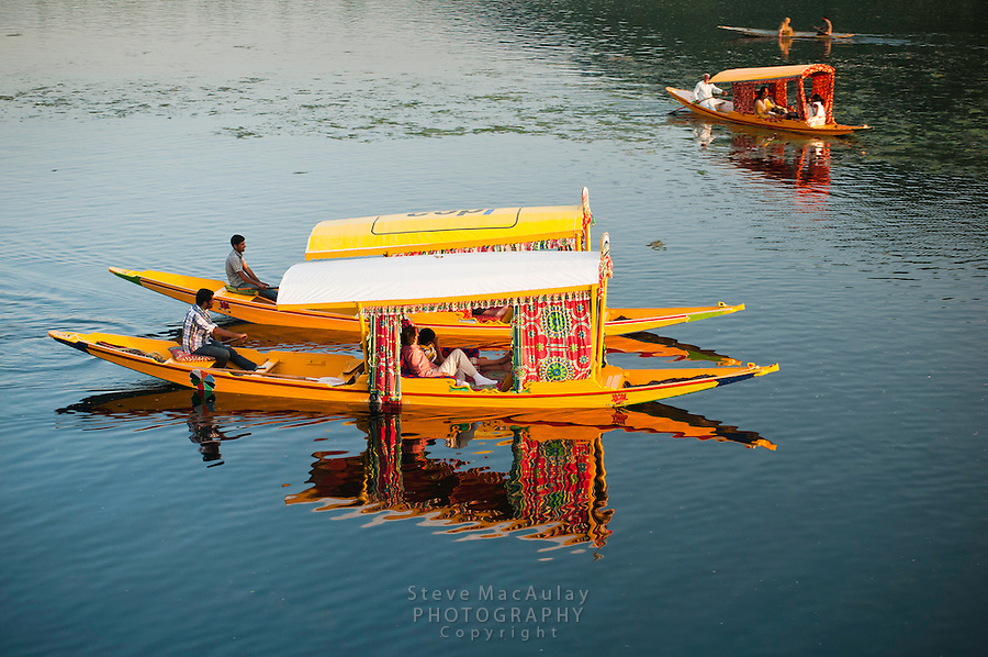 Traditional Kashmiri shikaras, or gondolas, paired up in symmetry, and reflected in Dal Lake, Srinagar, Kashmir, india..