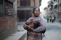 A woman holds two chickens in the street of Bhaktapur, near Kathmandu, Nepal. May 04, 2015