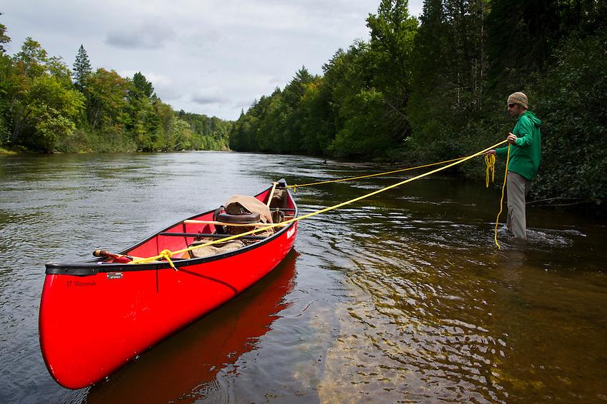 Lining a canoe above the Upper Falls of the Tahquamenon River near Newberry Michigan.