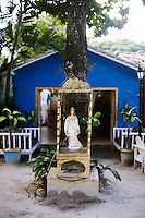 A statue of a Bahian deity adorns a tree outside a colonial house in Trancoso