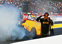 Mar 14, 2014; Gainesville, FL, USA; A crew member covers his ears as NHRA funny car driver Del Worsham burns out past him during qualifying for the Gatornationals at Gainesville Raceway Mandatory Credit: Mark J. Rebilas-USA TODAY Sports