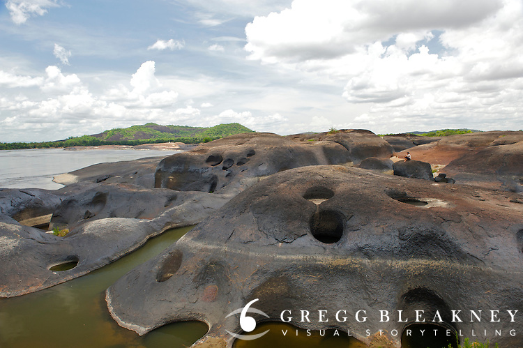 A Llanero plainsman rests atop a volcanic boulder field in the the middle of the Orinoco River - Orinoco River Basin - Venezuela/Colombia border - South America