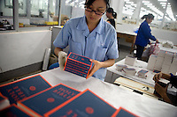 "Amity Printing Company employee arranges newly-printed English Standard Version Holy Bibles for shipment in the Amity Printing Company's new printing facility in Nanjing, China....On May 18, 2008, the Amity Printing Company in Nanjing, Jiangsu Province, China, inaugurated its new printing facility in southern Nanjing.  The facility doubles the printing capacity of the company, now up to 12 million Bibles produced in a year, making Amity Printing Company the largest producer of Bibles in the world.  The company, in cooperation with the international organization the United Bible Societies, produces Bibles for both domestic Chinese use and international distribution.  The company's Bibles are printed in Chinese and many other languages.  Within China, the Bibles are distributed both to registered and unregistered Christians who worship in illegal ""house churches."""