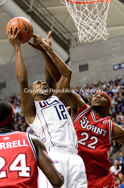 STORRS, CT- 08 JANUARY 2008- 010808JT09-<br /> UConn's A. J. Price is blocked by St. John's Sean Evans (22) during Tuesday's game in Storrs. In the foreground is St. John's Justin Burrell. UConn won 81-65.<br /> Josalee Thrift / Republican-American