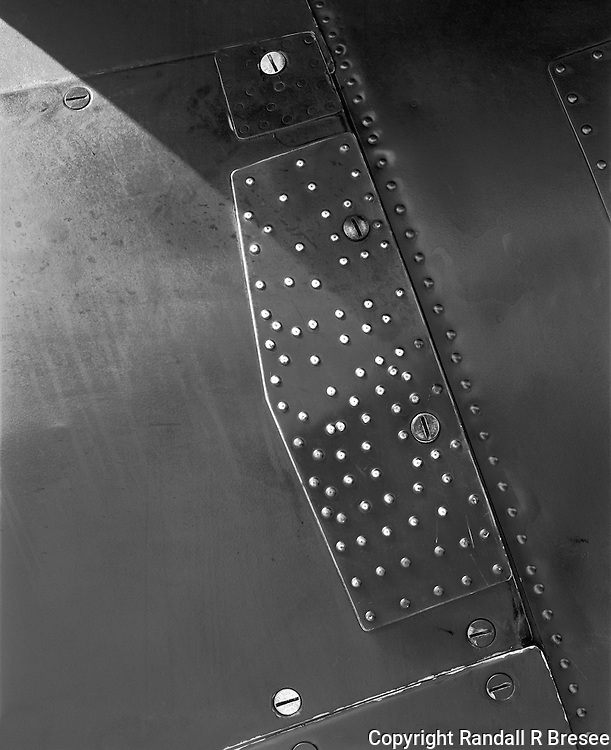 &quot;Metal Plate on a B-25 Bomber&quot; <br /> <br /> This black and white photo shows a metal plate attached to a B-25 &quot;Mitchell&quot; bomber. A huge number of rivets and screws secured the plate to the aircraft securely. The plane was piloted by Greg Vallero at the 2012 Memorial Day &quot;Salute to Veterans&quot; airshow in Columbia, Missouri.
