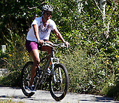 First Lady Michelle Obama rides a bike with daughter Sasha Obama (off camera) on bike path through Manuel F. Correllus State Forest in West Tisbury, Massachusetts while vacationing on Martha's Vineyard on August 23, 2011.    Photo by Matthew Healey.Credit: Matthew Healey / Pool via CNP