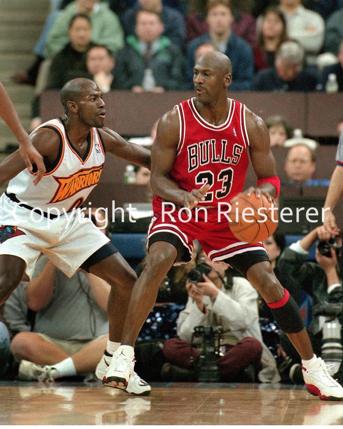 Chicago Bulls Michael Jordan with Golden State Warriors Tony Delk..(1998 Photo/Ron Riesterer)