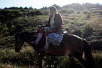BULGARIA, Ribnovo, June 20, 2009. A Bulgarian muslim woman rides a horse near the remote village of Ribnovo in the Rhodope Mountains. southern Bulgaria. Bulgarian Muslims, which today are nearly 8% of the country's population and the largest muslim minority community in the European Union, revived their cultural and religious traditions after the fall of communist regime in Bulgaria in 1989. .BULGARIE, Ribnovo, 20 Juin 2009. Une Bulgare de confession musulmane assise sur un cheval rentre des champs près du petit village de Ribnovo dans les montagnes des Rhodopes en Bulgarie. La minorité musulmane qui représente aujourd'hui près de 8% de la population totale du pays et qui est la plus large majorité musulmane dans les pays de l'Union Européenne a ravive ses traditions culturelles et religieuse après la chute du régime communiste Bulgare en 1989.
