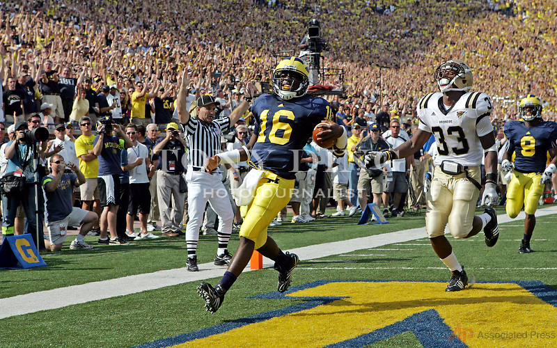 Michigan quarterback Denard Robinson (16) scores a touchdown on a 43-yard run, ahead of Western Michigan safety Mario Armstrong (33), in the first quarter of an NCAA college football game, Saturday, Sept. 5, 2009, in Ann Arbor, Mich. Michigan won 31-7. (AP Photo/Tony Ding)
