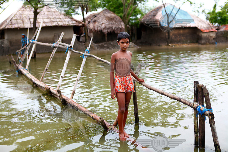 A boy stands on a temporary bridge that crosses flood waters in his village, one of many that have been innundated in the Satkhira district. Each year limited flooding helps to enrich the soil and create very fertile farm land. In turn, this results in a high population density on the flood plain. However, the low lying land is also prone to extreme flooding events that are very destructive and to both economy and life.