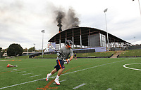 UVa lacrosse player Nick O'Reilly continues to practice with coach Marc Van Arsdale, behind, despite a large fire on the roof of the new UVa football practice facility Monday afternoon in Charlottesville, Va. Photo/Andrew Shurtleff