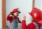 18 month old toddler boy looking in mirror recognizing self, wearing fire hat horizontal