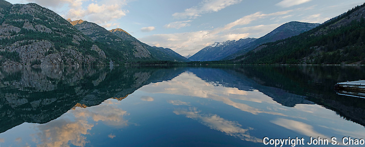 Daybreak reflections of sky and mountains on the north end of Lake Chelan in Stehekin, North Cascades National Park, Washington State.