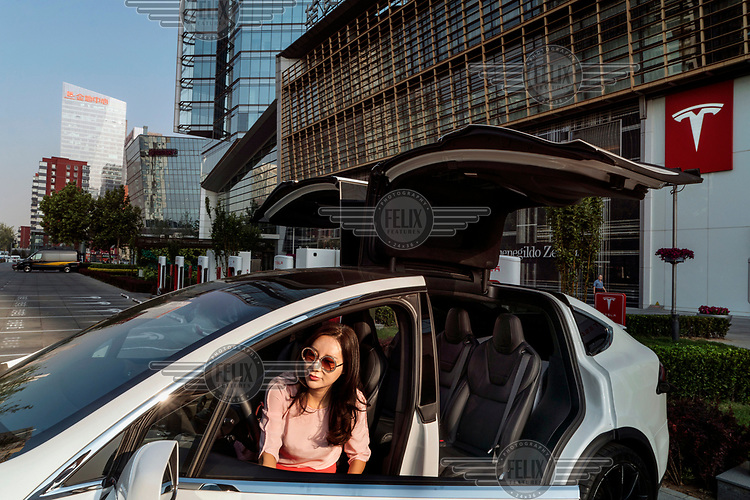 Vanessa Zhu gets out of her Tesla Model X at a charging station in front of a Tesla showroom at China Central Place mall.