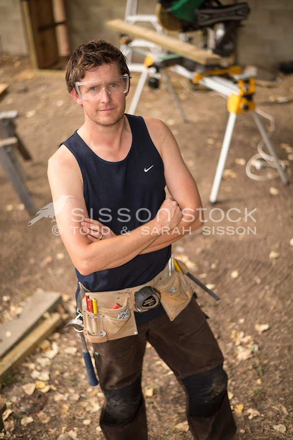 Home handyman | builder wearing safety glasses and standing in construction site, New Zealand- stock photo, canvas, fine art print