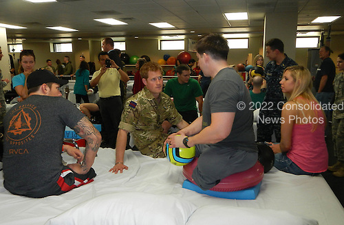 Britain's Prince Harry, center, talks with Army Staff Sgt. Tim Payne, right, and Navy Special Operator 2 Bo Reichenbach, left, wounded warriors undergoing treatment at Walter Reed National Military Medical Center in Bethesda, Md., May 10, 2013. .Mandatory Credit: Donna Miles / DoD via CNP
