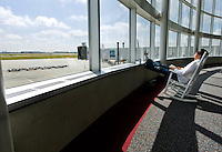 A passenger waits for his flight at Charlotte-Douglas International Airport. ..Charlotte-Douglas International Airport, one of US Airways' largest hubs, serves 10 major airlines, including Air Canada, Air Tran, American, Continental, Delta, JetBlue, Lufthansa, Northwest and United. The airport is the nation?s 10th largest in terms of total operations, the 18th largest in terms of total passengers and the 37th largest in terms of cargo. Charlotte-Douglas serves 640 daily flights, including direct flights to 120 cities. ..Photographer has series of images from Charlotte-Douglas International Airport, including aerials. ... PATRICK SCHNEIDER PHOTO.COM