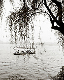 CHINA, Hangzhou, people traveling in a boat on West Lake (B&W)
