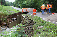 NWA Democrat-Gazette/DAVID GOTTSCHALK Personnel with the Arkansas Department of Transportation survey Friday, June 7, 2019, the area around a bridge on Arkansas 265 in Hogeye after the creek it spans washed away the roadbed during heavy rains Thursday evening. The highway is closed south of the Arkansas 156 intersection.