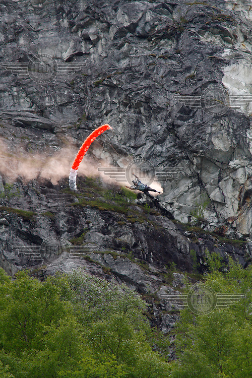 Parachute jumper trailing smoke near Gudvangen. The Extremesport Week, Ekstremsportveko, is the worlds largest gathering of adrenalin junkies. In the small town of Voss enthusiasts in a varitety of extreme sports come togheter every summer to compete and play.© Fredrik Naumann