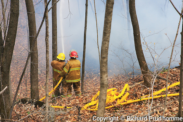 Two firemen watering down a forest fire in Rawdon, Quebec
