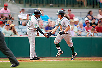 Daytona Tortugas coach Desi Relaford (25) congratulates TJ Friedl (6) after hitting a home run in the top of the fifth inning during a game against the Florida Fire Frogs on April 7, 2018 at Osceola County Stadium in Kissimmee, Florida.  Daytona defeated Florida 4-3 in a six inning rain shortened game.  (Mike Janes/Four Seam Images)