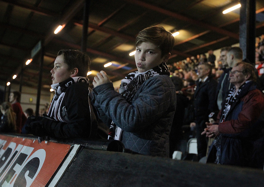 A young Grimsby Town fan looks dejected as his side lose their 2 -1 lead in the final minutes of the match<br /> <br /> Photo by Rich Linley/CameraSport<br /> <br /> Football - FA Challenge Cup Third Round - Grimsby Town v Huddersfield Town - Saturday 4th January 2014 - Blundell Park - Grimsby<br /> <br />  &copy; CameraSport - 43 Linden Ave. Countesthorpe. Leicester. England. LE8 5PG - Tel: +44 (0) 116 277 4147 - admin@camerasport.com - www.camerasport.com