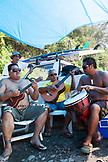 FRENCH POLYNESIA, Tahiti. Local surfers at Papenoo Beach playing instruments.