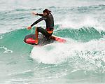 A boogie board surfer enjoying small waves on Shipwreck Beach, Po'ipu Bay, Kaua'i, Hawaii
