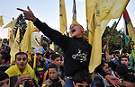 Palestinian Fatah supporter shout slogans during a gathering to celebrate the fiftieth anniversary of the start of the Fatah movement, in Gaza city on December 31, 2014. The Fatah movement was founded by the late iconic leader Yasser Arafat in the 1950s and formally launched its armed struggle against Israel on January 1, 1965. Photo by Mohammed Talatene