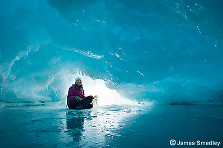 Woman and her pet dog sitting inside a natural ice cave on frozen Lake Superior.