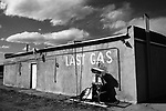 """a broken gas pump against an adobe wall with words """"last gas"""" written on the wall comments on the state of energy supply and demand in the world in the 21st century, big chief gas station, san ysidro, new mexico, usa"""