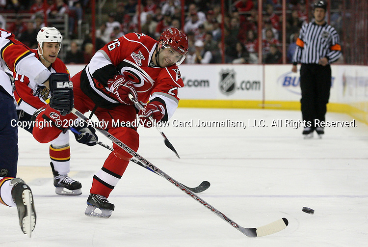 04 April 2008: Carolina's Erik Cole (26) dumps the puck past Florida's Jay Bouwmeester (4). The Florida Panthers defeated the Carolina Hurricanes 4-3 at the RBC Center in Raleigh, NC in a 2007-08 National Hockey League regular season game.