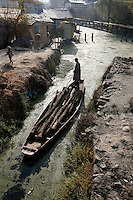 A man transports wood on a polluted canal linked to the Dal Lake.Srinagar, Kashmir, India. © Fredrik Naumann/Felix Features