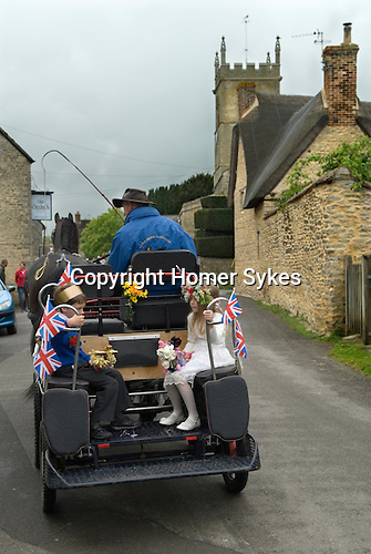 Charlton-on-Otmoor Oxfordshire 1st of May Day Celebrations. Children from the Church of England St Mary the Virgin Primary School process to the village church to have their May garlands blessed. Seen here the May Queen and King get a lift to the church. 2014.