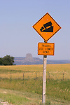 Road sign and Devils Tower in the background